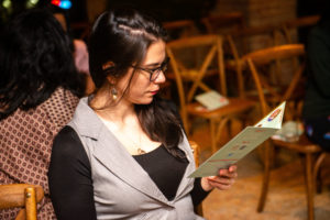 A dark haired woman with glasses reading an event program.