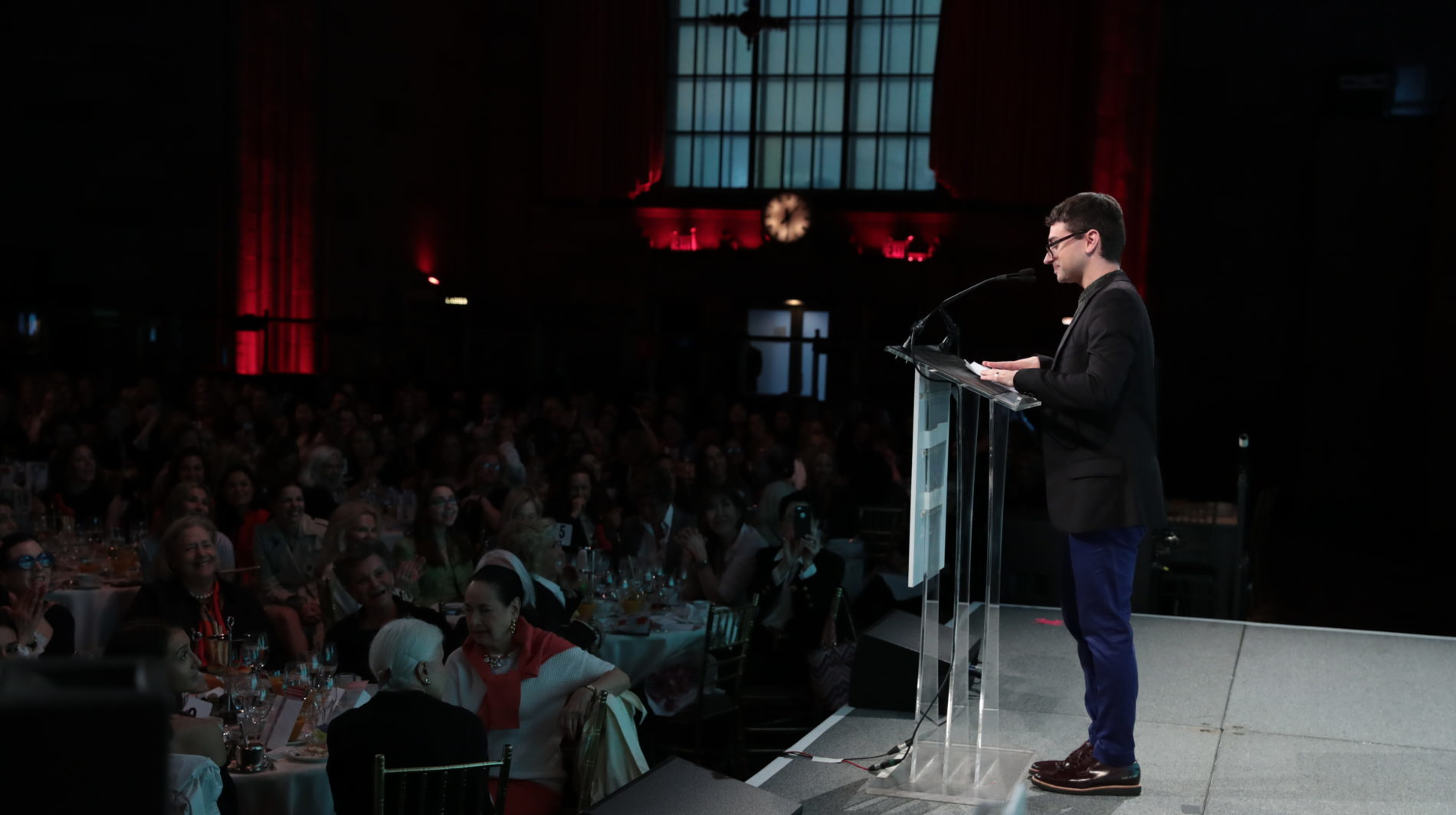 Christian Siriano standing at podium in front of crowd at luncheon