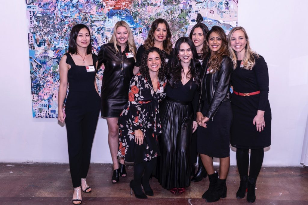 a group of women standing in front of a painting at a gallery